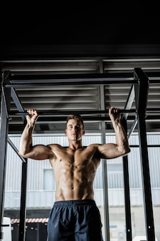 Shirtless man doing pull up at the gym