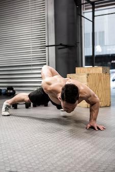 Shirtless man doing push up at the crossfit gym