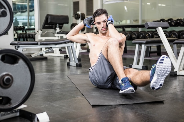 Shirtless man doing sitting up in the gym