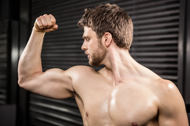 Shirtless man flexing biceps at the crossfit gym