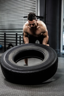 Shirtless man flipping heavy tire at the crossfit gym