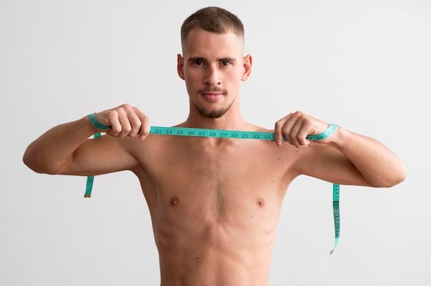 測定テープを保持している上半身裸の男