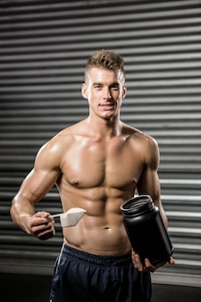 Shirtless man holding protein powder at the  gym