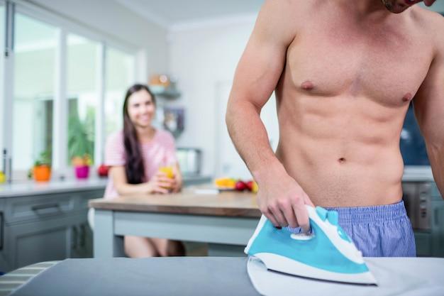 Shirtless man ironing in kitchen while girlfriend is watching him