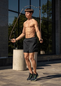 Shirtless man jumping rope outdoors