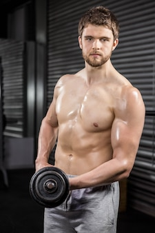Shirtless man lifting heavy dumbbell at the crossfit gym