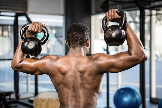 Shirtless man lifting heavy kettlebells at the crossfit gym