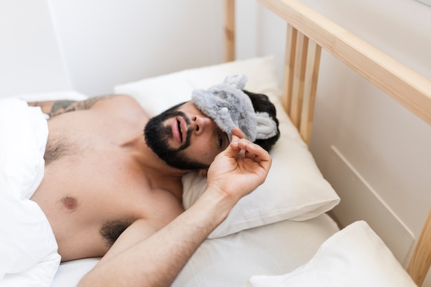Shirtless man lying on bed peeking from an eye mask