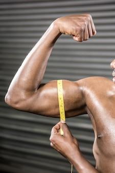 Shirtless man measuring biceps at the crossfit gym