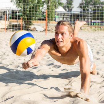 Shirtless man playing volleyball on the beach