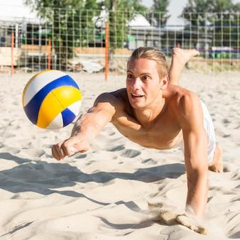 上半身裸の男がビーチでバレーボールをプレー