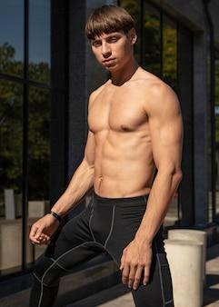 Shirtless man posing outdoors while exercising