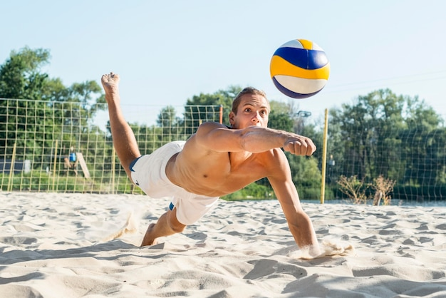 Shirtless man reaching to hit ball on the sand while playing volleyball