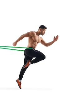 Shirtless man running in place using resistance band.