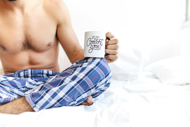 Shirtless man sitting on bed with cup of coffee