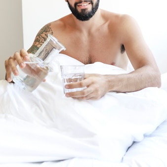 Shirtless man sitting on bed with glass of water