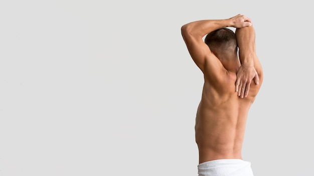 Shirtless man stretching his arms with copy space