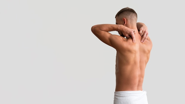 Shirtless man in a towel stretching his arms with copy space