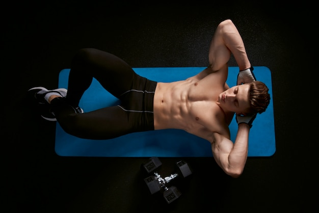 Shirtless man training abs on mat.