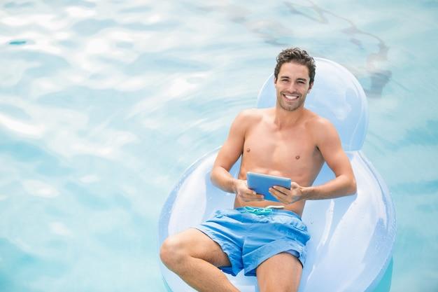 膨脹可能なリングにデジタルタブレットを使用して上半身裸の男