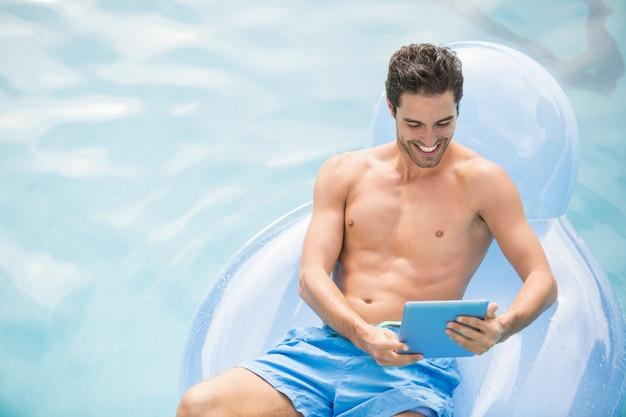 水泳リングにデジタルタブレットを使用して上半身裸の男