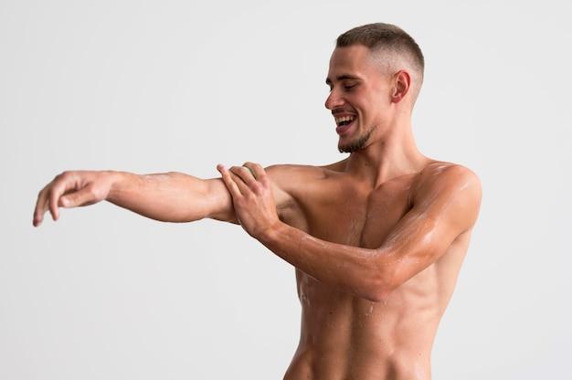 Shirtless man washing himself