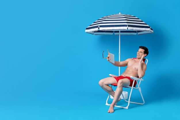 Shirtless man waving hand on video call while sitting on beach chair