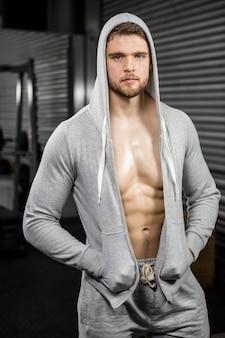 Shirtless man wearing jumper at the gym