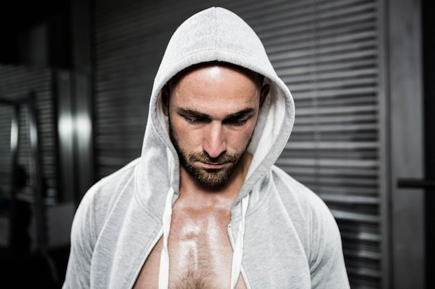 Shirtless man wearing jumper looking down at the crossfit gym