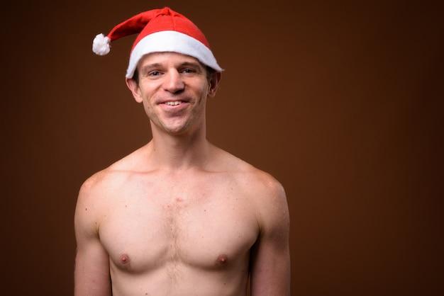 갈색 벽에 크리스마스 산타 모자 준비 입고 shirtless 남자