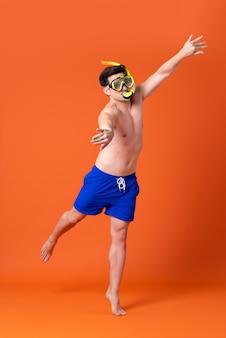 Человек без рубашки в маске для снорклинга делает жест плавания