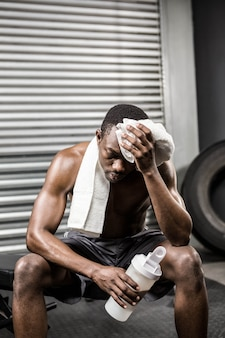 Shirtless man wiping sweat with towel at the crossfit gym