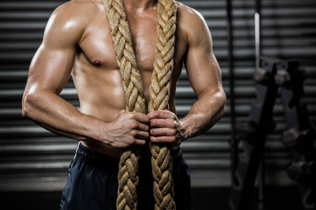 Shirtless man with battle rope around neck at the gym