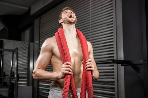Shirtless man with battle rope around neck shouting at the crossfit gym