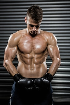 Shirtless man with boxing gloves at thegym