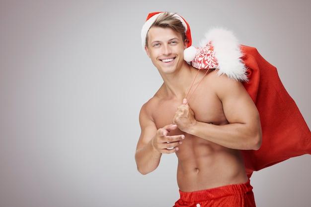 クリスマスの袋を持つ上半身裸の男