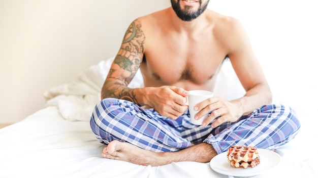 Shirtless man with cup of coffee and waffle sitting on bed