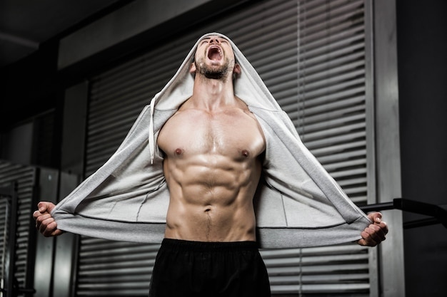 Shirtless man with grey jumper shouting at the crossfit gym