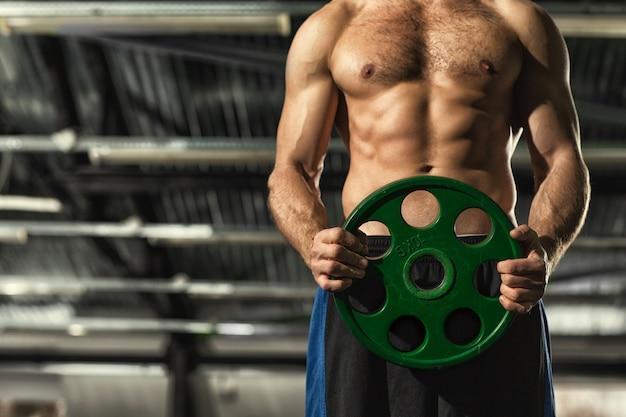 ホットセクシーなトーンの筋肉の強い胴体バーベルウェイトプレートを保持している上半身裸の男