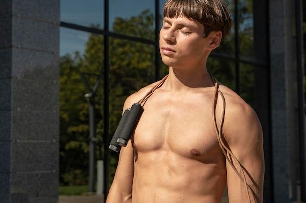 屋外で縄跳びと上半身裸の男