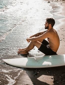 바다를 흔들며 근처 편안한 서핑 보드와 벗은 남자