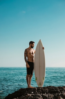 Shirtless man with surfboard standing on rock