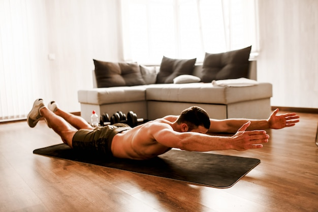 Shirtless man working out at home