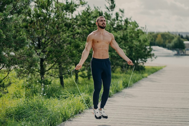 Shirtless man working out outdoors with jump rope
