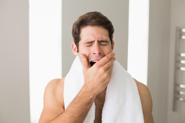 Shirtless man yawning with eyes closed at home