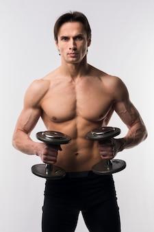 Мускулистый мужчина без рубашки позирует с весами