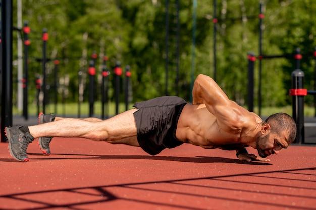 Мускулистый спортсмен без рубашки держит свое тело вытянутым над землей, опираясь на левую руку, а другую на спину