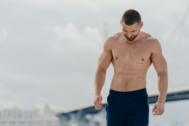 Shirtless muscular bodybuilder walks outdoors takes break after physical exercises concentrated down has strong athletic body. fit bearded sportsman trains in open air. sporty lifestyle concept