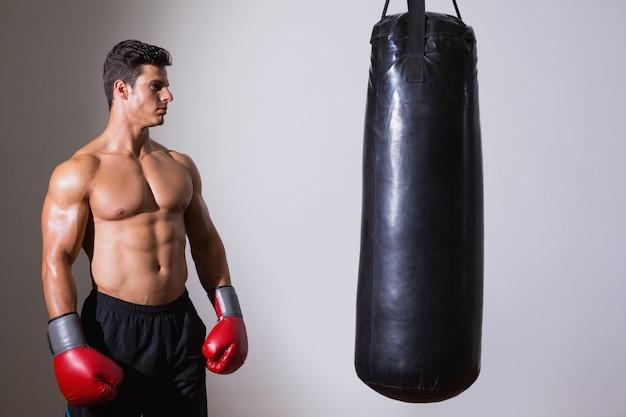Shirtless muscular boxer looking at punching bag