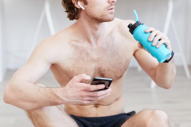 Мускулистый мужчина без рубашки пьет воду и использует свой мобильный телефон после спортивной тренировки